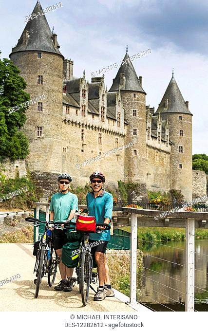 Cycling couple with bikes along a riverside pathway and old stone castle with large turrets in the background; Josseline, Brittany, France