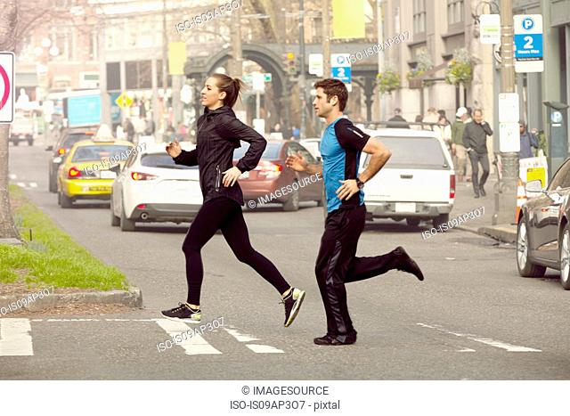 Young man and woman running across city road