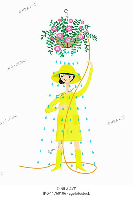 Woman wearing rain hat, raincoat and wellingtons to water hanging basket