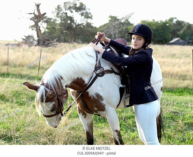 Portrait of teenage girl preparing to mount horse