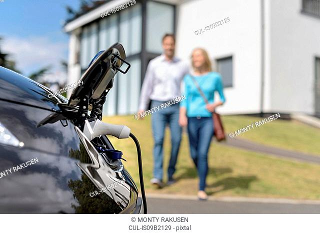 Man and woman walking towards electric car being charged
