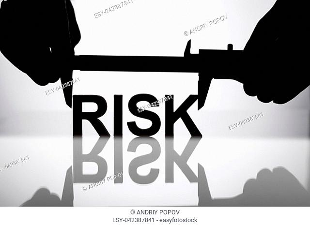 Silhouette Of A Businessperson's Hand Measuring Risk Word With Vernier Caliper On Reflective Desk