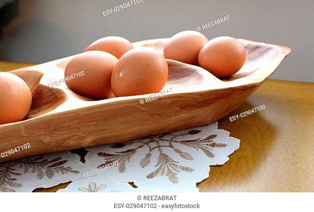Beautiful crafted wood tray holding several fresh cage-free brown eggs