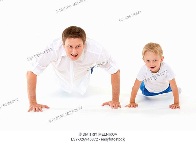 Young father with child are doing gymnastic exercises on a white background. Healthy lifestyle. Push-ups