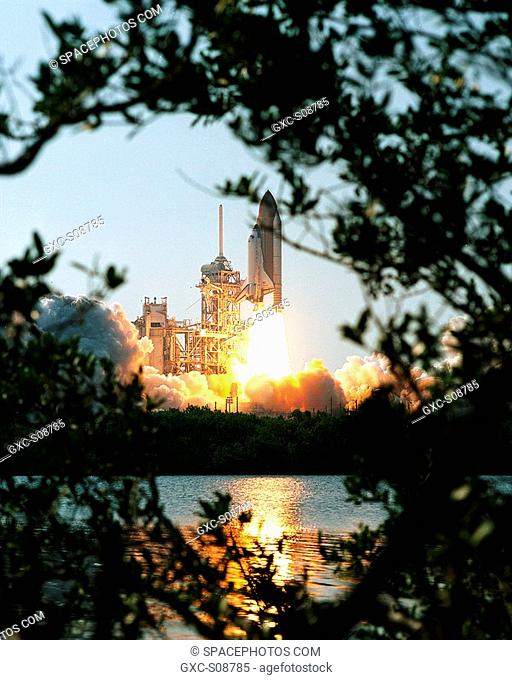 08/10/2001 -- Trees frame Space Shuttle Discovery trailing columns of fire from the solid rocket boosters as it soars into the blue sky on mission STS-105 to...