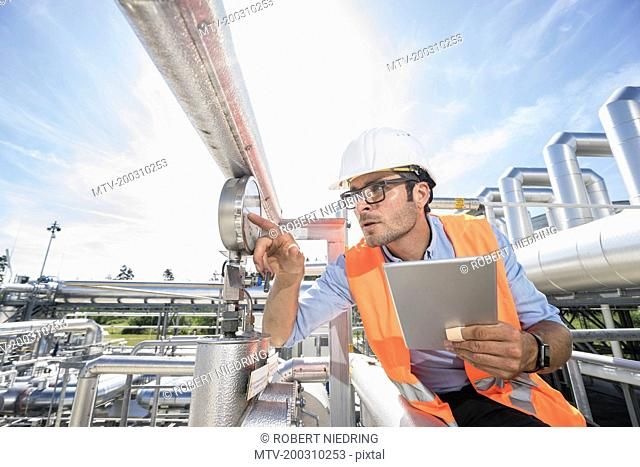 Male engineer controlling measuring instrument at geothermal power station, Bavaria, Germany