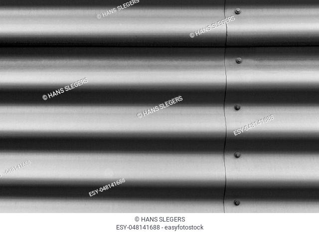 Detail of silver corrugated metal with bolts
