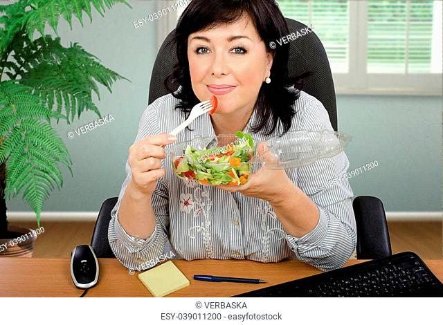 Black haired woman eating vegetable salad from transparent plastic container at office desk