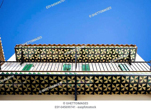 Azulejos (translation: typical Spanish tiles) on the bottom of balconies in the historic center of Sitges, Spain