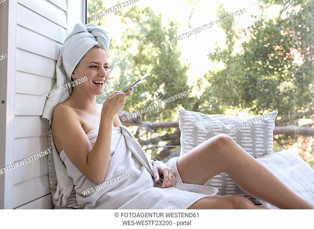 Laughing young woman wrapped in a towel holding cell phone