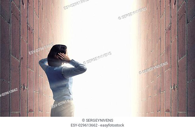 Young frustrated woman standing with back covering ears with arms