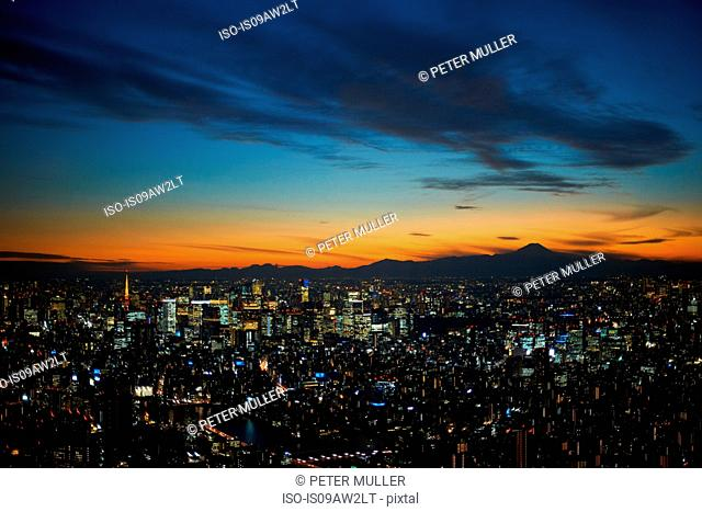 Elevated cityscape view with sunset over silhouetted Mount Fuji, Tokyo, Japan