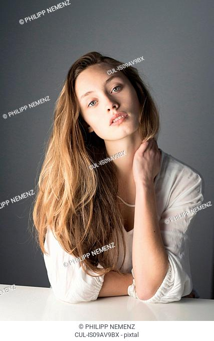 Studio portrait of beautiful mid adult woman with long brown hair resting on elbows