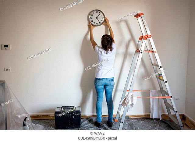 Senior woman putting up clock on house interior white wall, rear view