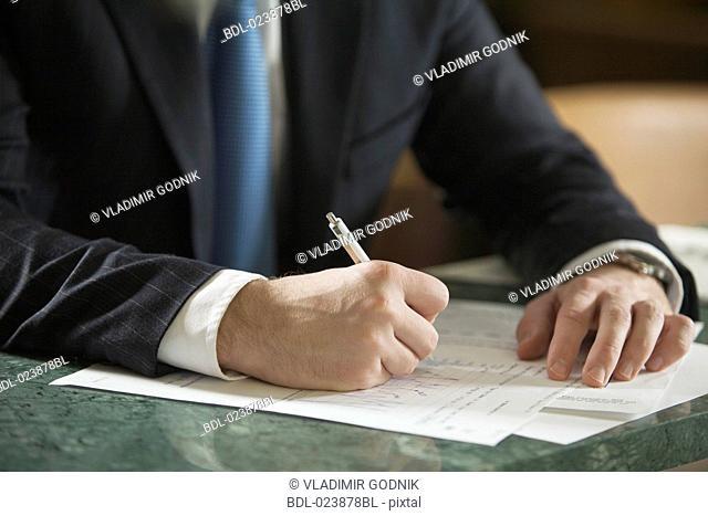 close-up of businessman writing document