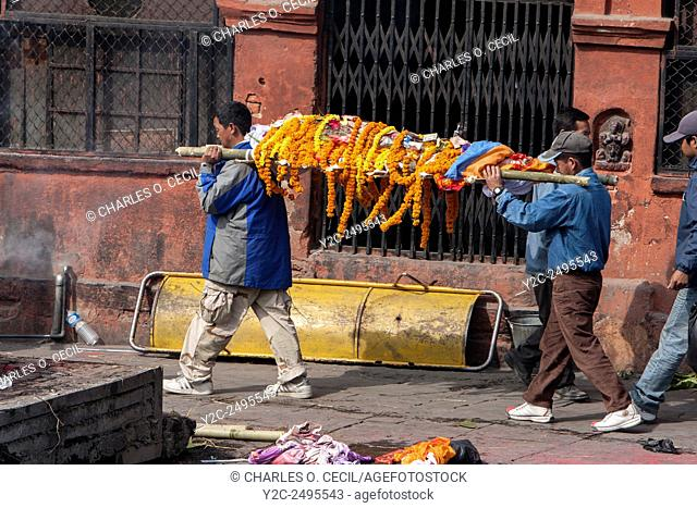 Nepal, Pashupatinath. Cremation Stages. Carrying a Corpse, covered in Marigolds and a White Sheet, to the Ghat, the cremation site