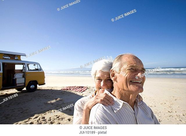Senior couple on beach by camper van, woman behind man, smiling, close-up