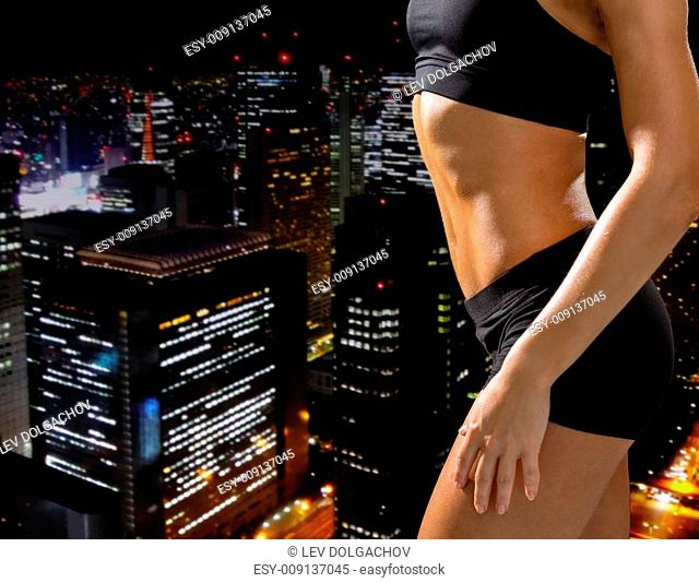 fitness and diet concept - close up of beautiful athletic female abs in sportswear