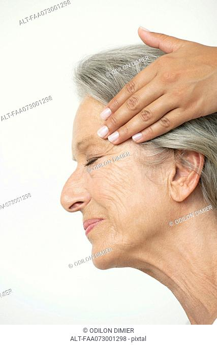 Senior woman having her temples massaged, cropped