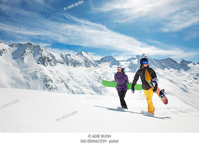 Two snowboarders walking in snow, Obergurgl, Austria
