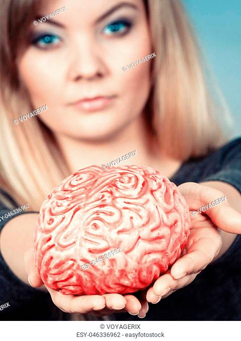 Blonde woman holding brain having something on mind, thinking of solution idea