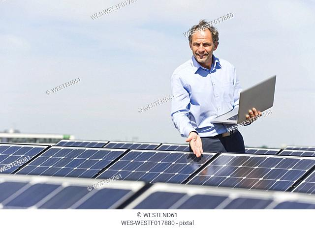 Germany, Munich, Mature man with laptop in solar plant, portrait