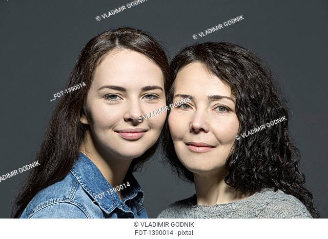 Portrait of smiling mother and daughter against over gray background