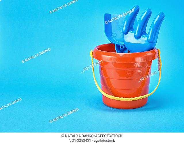 baby plastic red bucket and shovel with a rake on a blue background, copy space