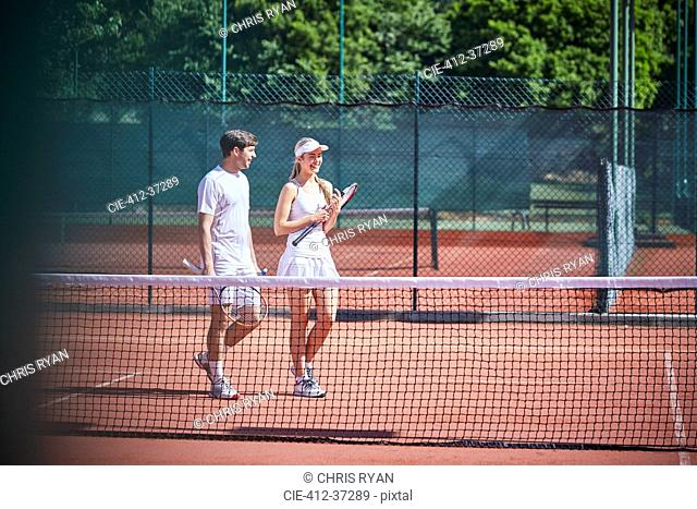 Young tennis player couple walking with tennis rackets on sunny clay tennis court