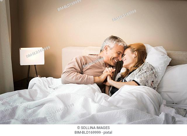 Smiling couple holding hands on bed