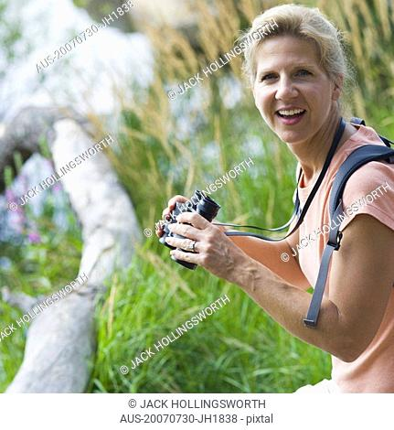 Portrait of a mature woman holding binoculars in a forest and smiling