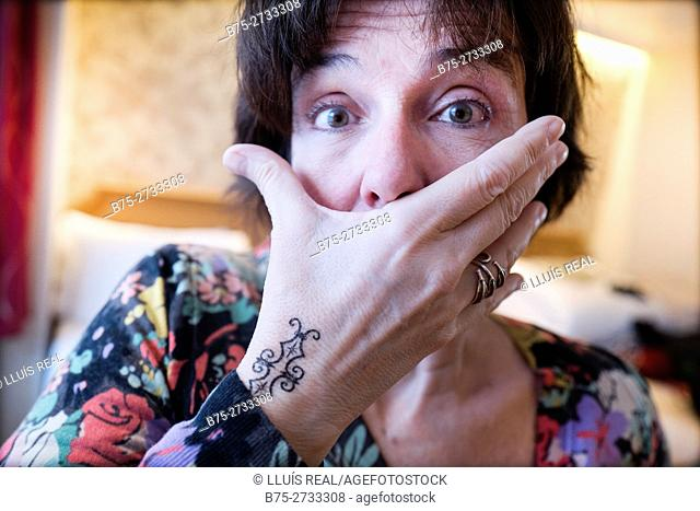 Woman covering her mouth with a tattoeed hand, surprised look