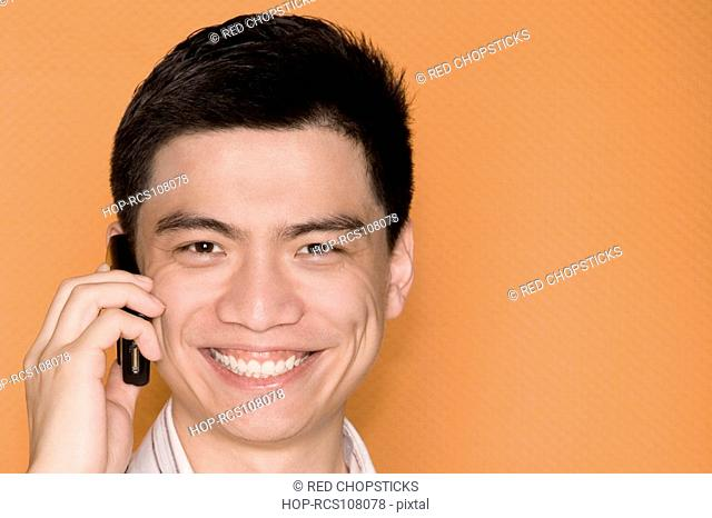 Portrait of a male office worker talking on a mobile phone and smiling