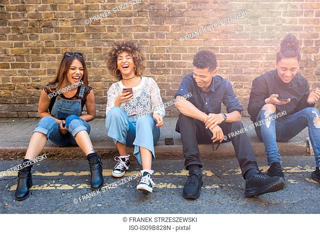 Four friends sitting in street, laughing, young woman holding smartphone