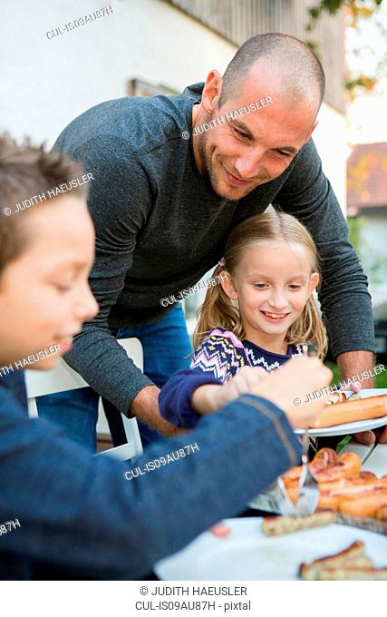 Father helping children at garden barbecue table