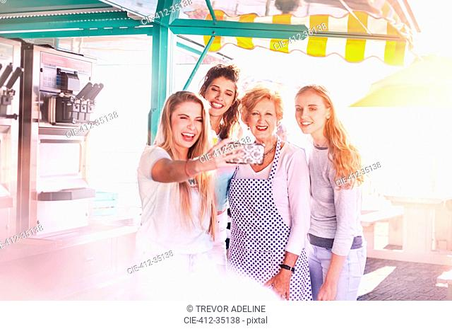 Young women taking selfie with senior business owner outside sunny food cart