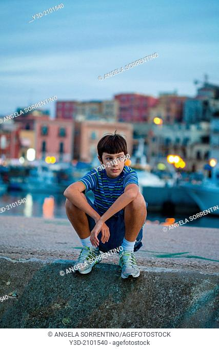 Young boy at evening on harbor of Naples, Italy