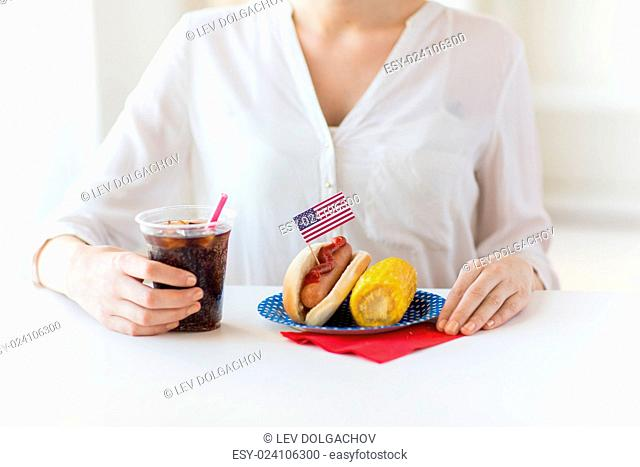 american independence day, celebration, patriotism and holidays concept - close up of woman hands with hot dog and corn holding cola drink in plastic cup on 4th...