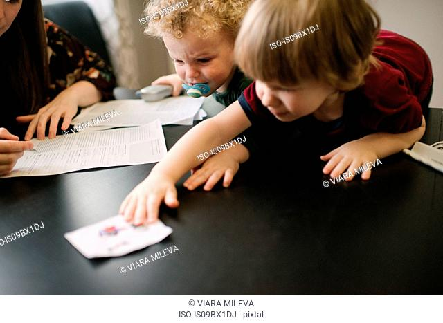 Mother filling form with sons playing at table