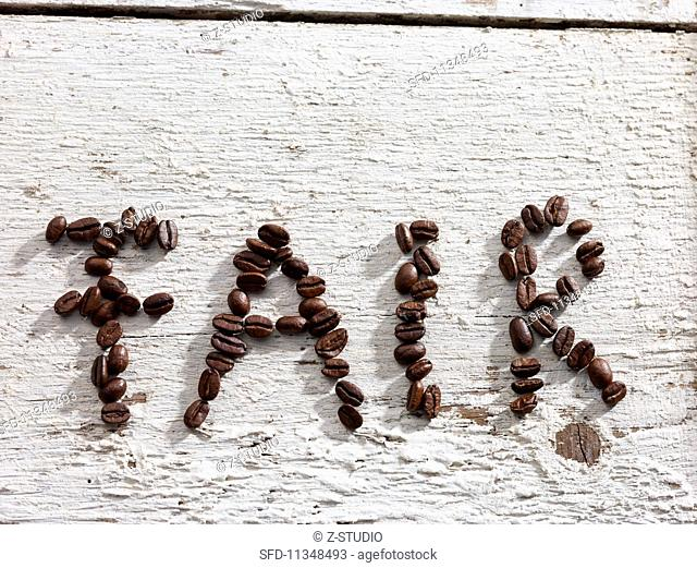 The word FAIR spelt out in coffee beans on white floor boards