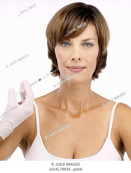 Studio shot of gloved hand with syringe next to woman's face
