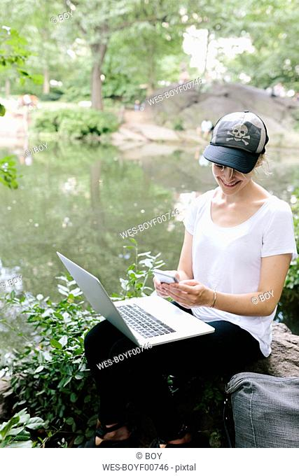 Young woman sitting at lakeside in park using cell phone and laptop