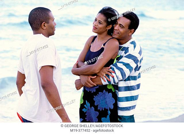 couple and a friend talk at the beach
