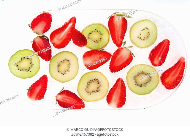 Series of slices of kiwi fruit and frozen strawberries