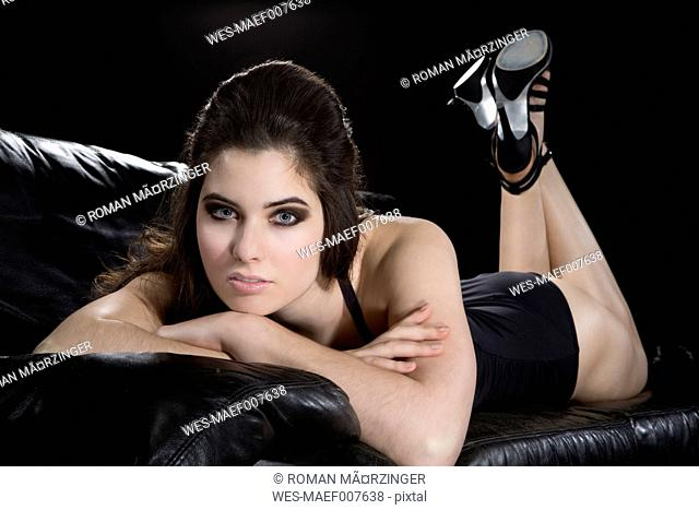 Young woman wearing black bathing suit and high heels lying on black leather couch