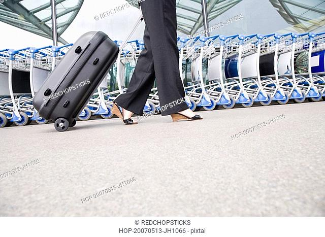 Low section view of a businesswoman pulling luggage outside an airport