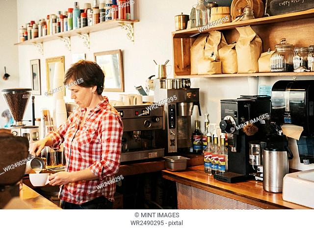 A woman in a plaid shirt working behind the counter in a coffee shop