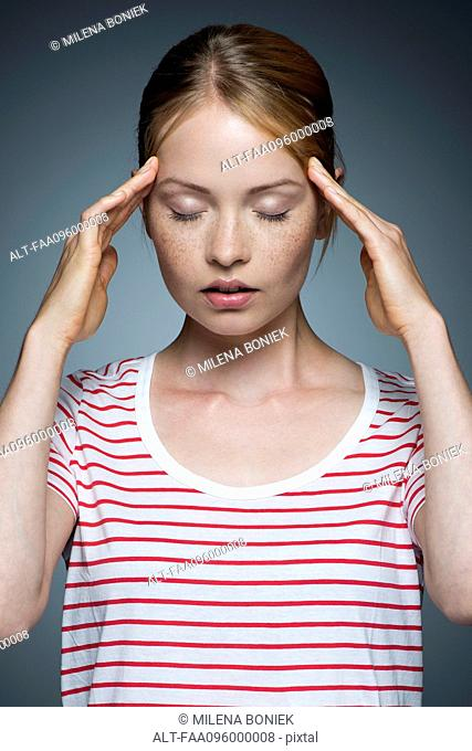 Young woman pressing sides of head