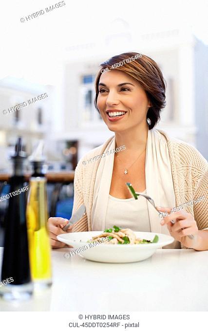 Woman eating at sidewalk cafe