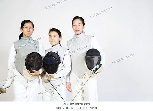 Portrait of three female fencers holding fencing foils and fencing masks